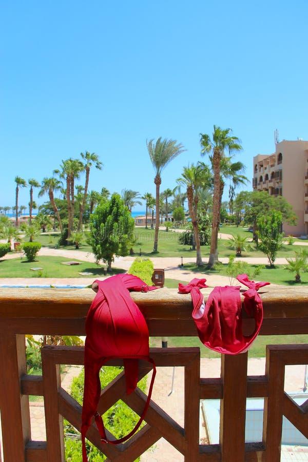 Le maillot de bain rouge des femmes est séché sur la clôture du balcon à la station de vacances Apprécier des vacances photos libres de droits