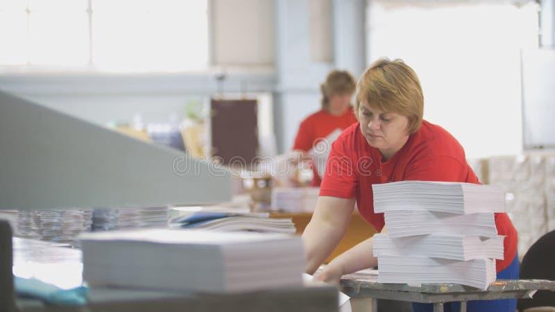 Le main-d'œuvre féminine démonte une pile de papier dans la typographie image stock