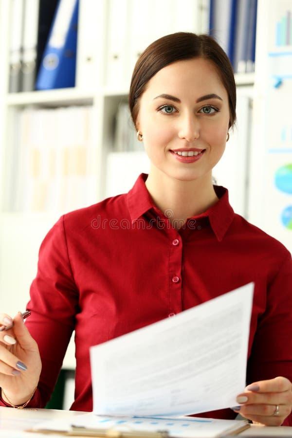 Le main-d'œuvre féminine de sourire attirant s'asseyent à la table de travail en papier de document de participation de bureau images libres de droits