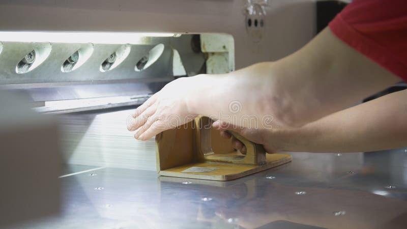 Le main-d'œuvre féminine plie une pile de papier dans la typographie photo stock