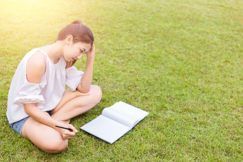 Le mal de tête de femmes Les femmes est sur l'herbe le livre est sur le genou photographie stock libre de droits
