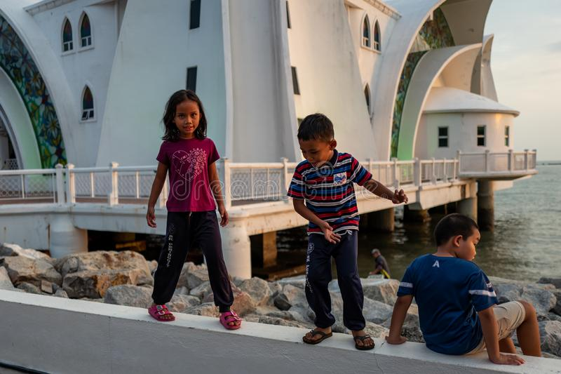 Le Malacca, Malaisie - 28 février 2019 : les enfants jouent dans le fron de la mosquée de détroits du Malacca connue sous le nom  photos libres de droits