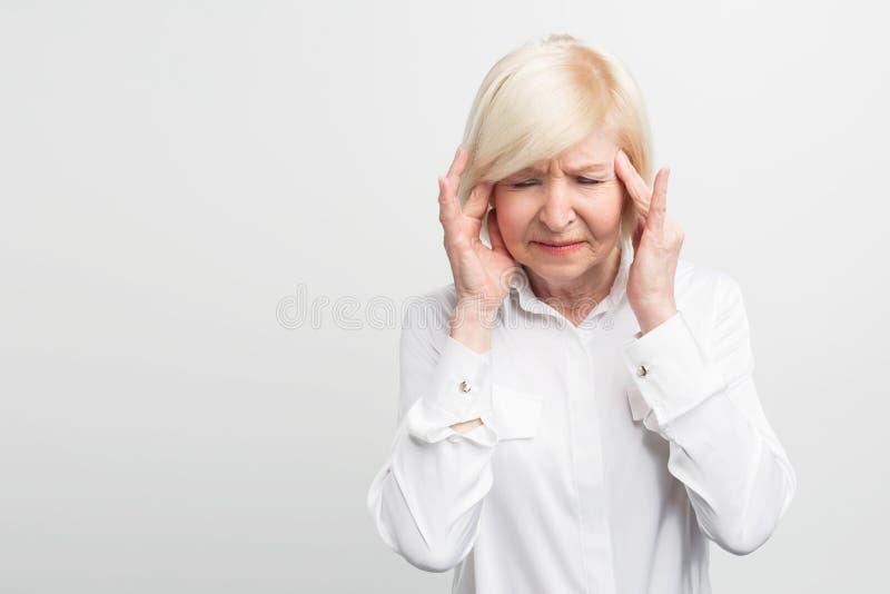 Le malade et la dame âgée touche son apparence de tête qu'elle a un mal de tête Elle sera fatigué probablement Fin vers le haut S photographie stock
