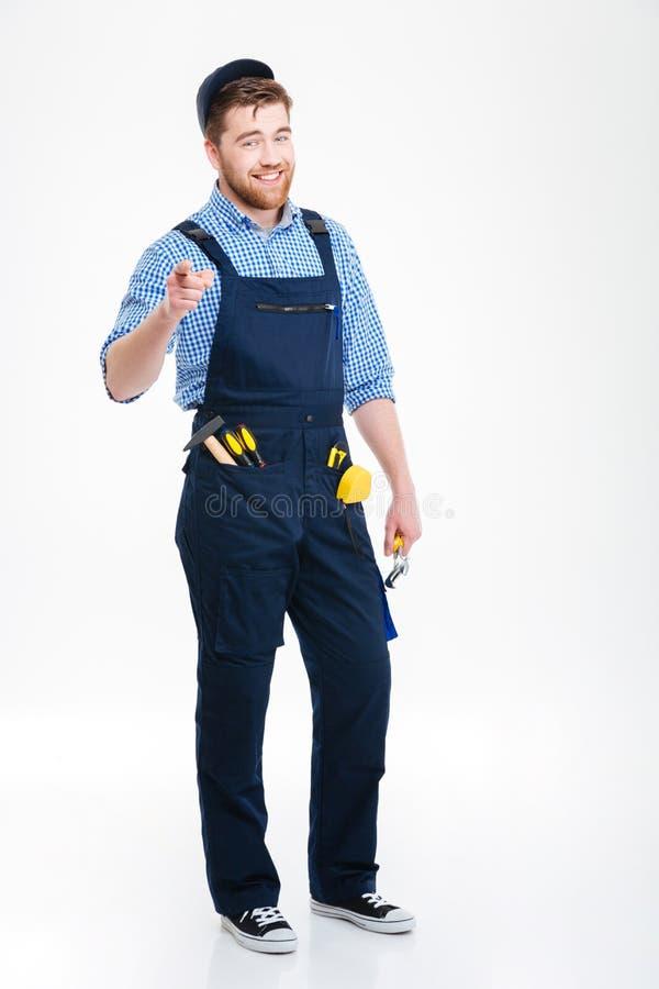 Le manbyggmästaren i overall och lock som pekar på dig arkivfoton