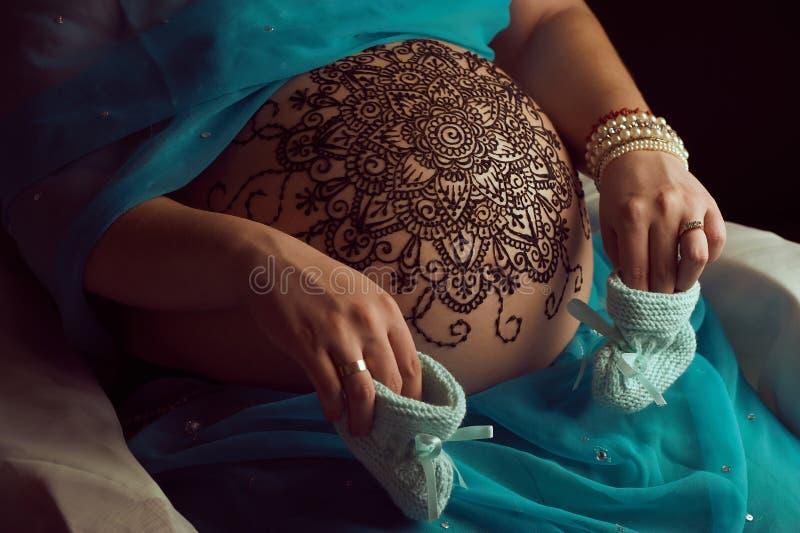 Le mandala avec le henné sur des woman's d'une grossesse se gonflent image libre de droits