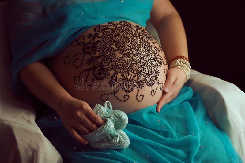 Le mandala avec le henné sur des woman's d'une grossesse se gonflent photographie stock libre de droits