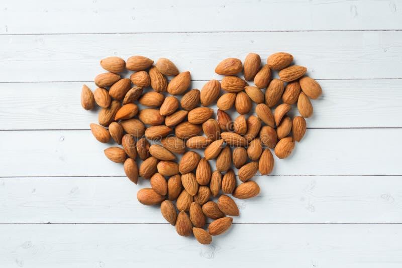 Le mandorle sono sciolte sotto forma di un cuore sulla tavola Fuoco selettivo fotografia stock