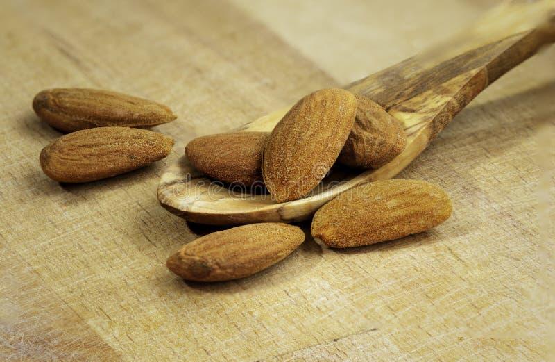 Le mandorle versano dal cucchiaio di legno sulla tavola di legno immagini stock libere da diritti