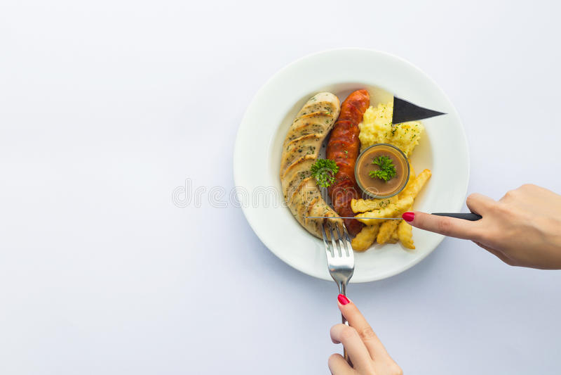 Le mani affetta le salsiccie arrostite con il ketchup della salsa su un piatto top fotografia stock libera da diritti