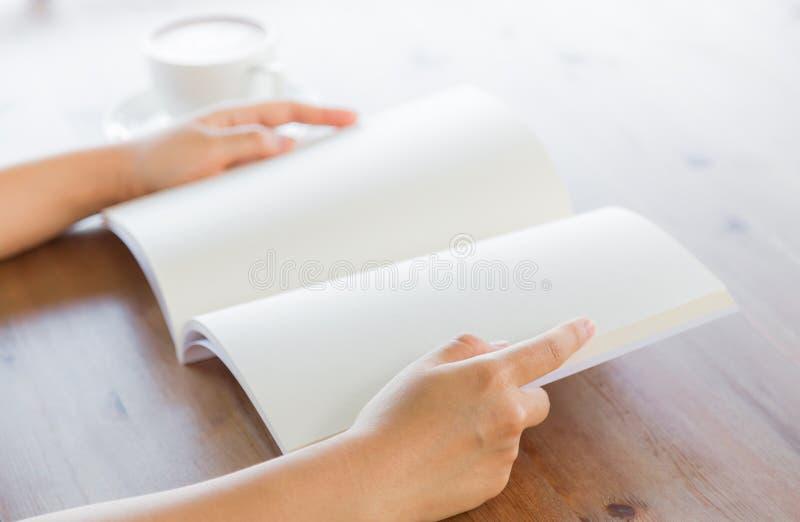 Le mani aprono il catalogo in bianco, riviste, derisione del libro su sulla tavola di legno fotografia stock libera da diritti