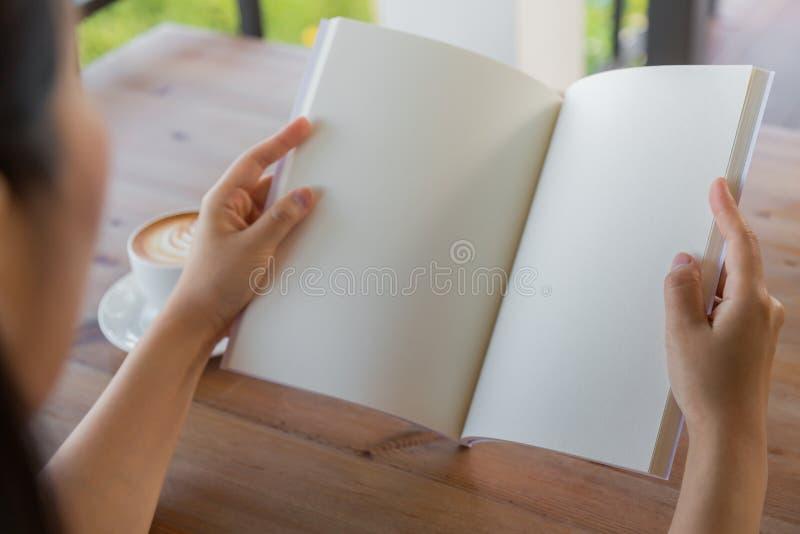 Le mani aprono il catalogo in bianco, riviste, derisione del libro su sulla tavola di legno immagini stock