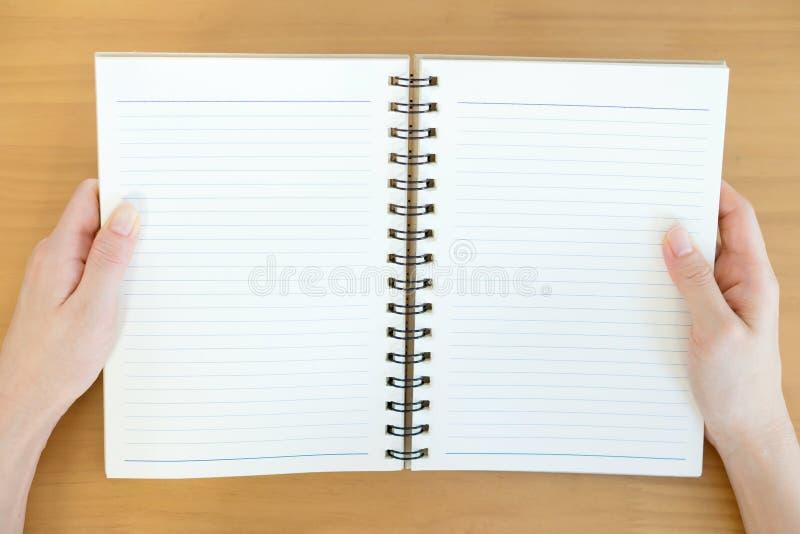 Le mani aprono il catalogo in bianco, riviste, libro fotografie stock