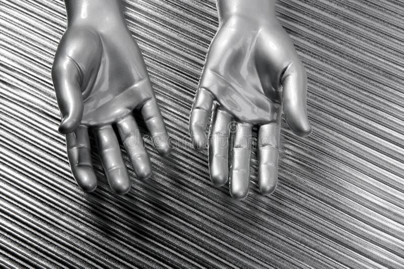 Le mani aprono l'acciaio futuristico dell'argento del robot sopra gray fotografie stock libere da diritti