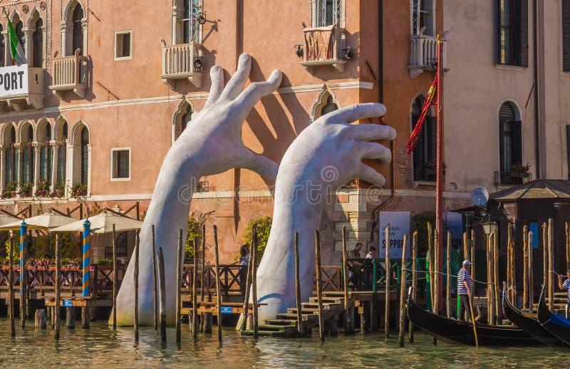 Le mani aumentano dall'acqua a Venezia per evidenziare il mutamento climatico fotografie stock