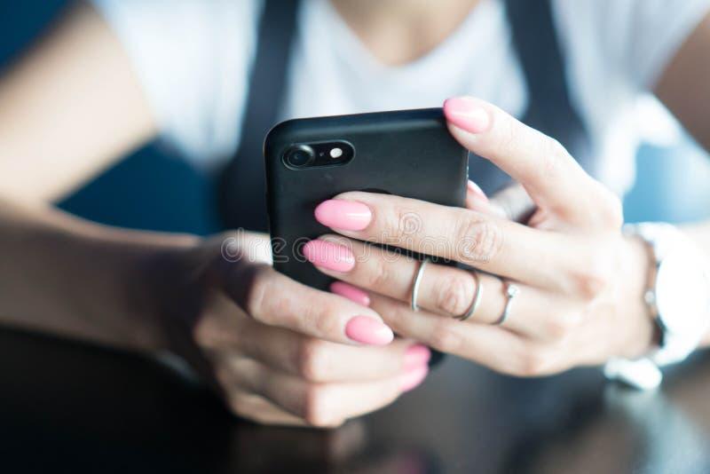 Le mani ben curato della ragazza con il manicure rosa tengono lo smartphone Una ragazza che per mezzo di uno smartphone compone u immagine stock libera da diritti