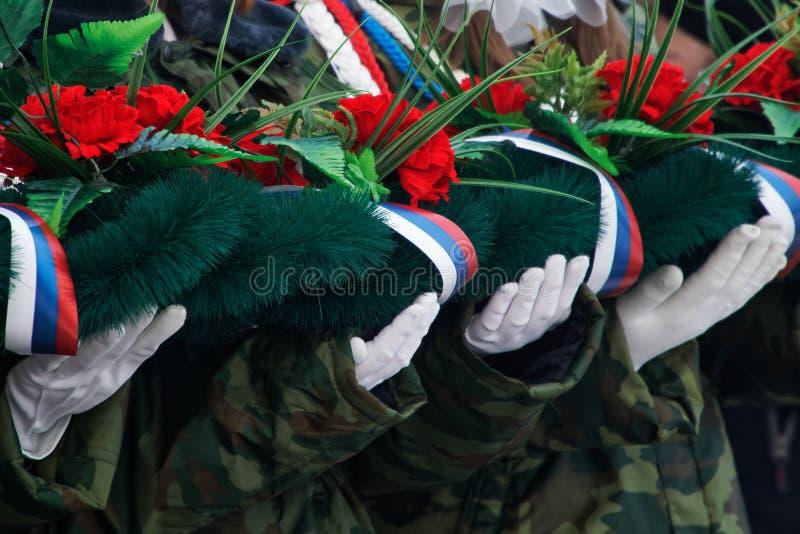 le mani Bianco-gloved tengono una corona ed i fiori in memoria di quelli uccisi nelle guerre e nei conflitti armati immagine stock