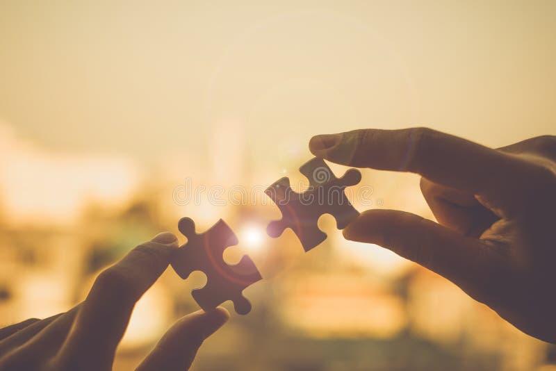 Le mani che collegano le coppie imbarazzano il pezzo contro effetto dell'alba immagini stock libere da diritti