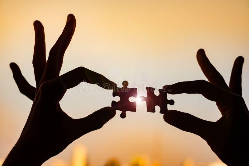 Le mani che collegano le coppie imbarazzano il pezzo contro effetto dell'alba fotografia stock libera da diritti