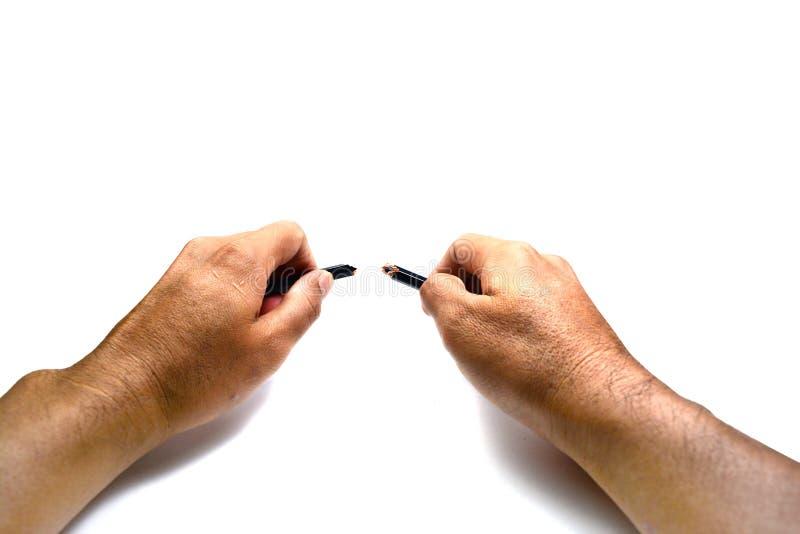 le mani che giudicano una matita rotta su fondo bianco isolata fotografia stock