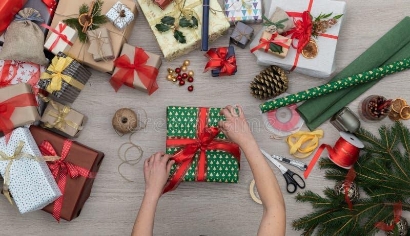 Le mani che preparano il contenitore attuale di regalo in tavola di legno verticale di vista superiore in pieno dei regali di nat fotografie stock libere da diritti