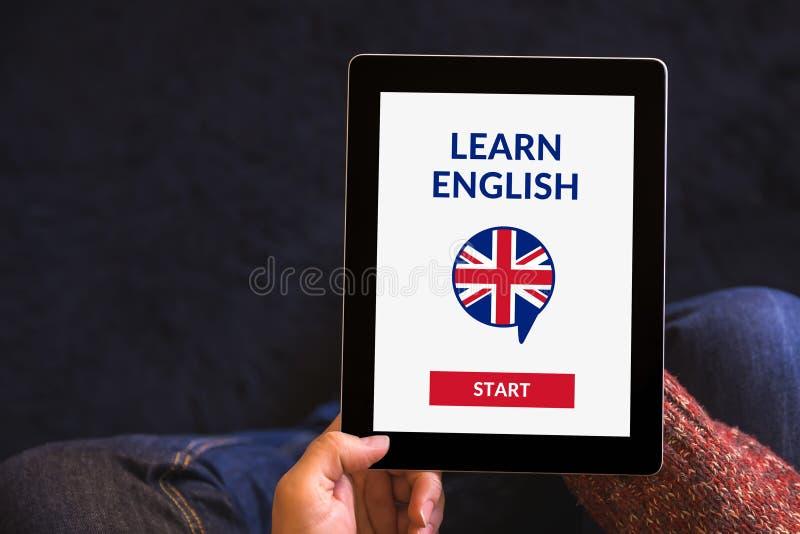 Le mani che tengono la compressa con online imparano il concetto inglese sul ghiaione fotografia stock libera da diritti