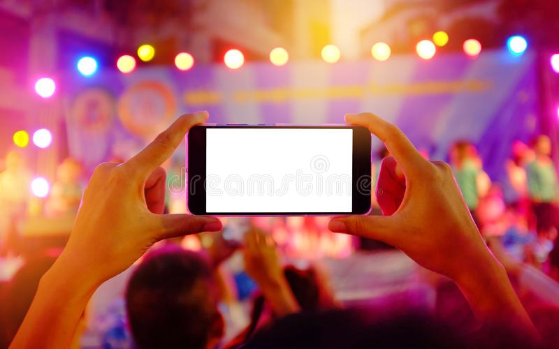 Le mani che tengono uno smartphone mobile registra il concerto in tensione variopinto con lo schermo bianco in bianco fotografia stock