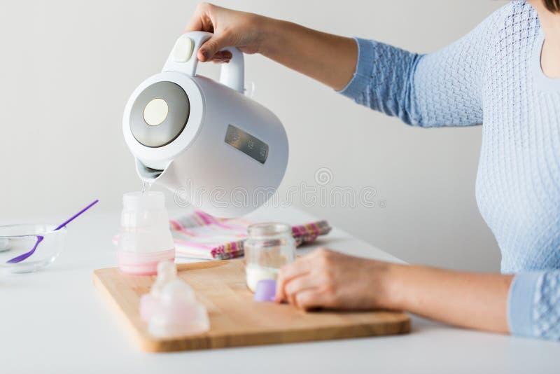 Le mani con il bollitore e la bottiglia che fanno il bambino mungono fotografia stock