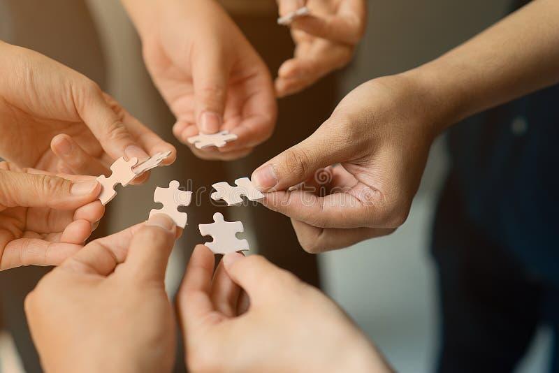 Le mani con il puzzle si uniscono come gruppo immagini stock