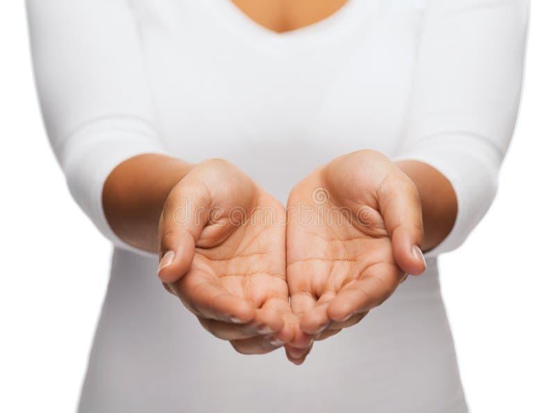 Le mani a coppa della donna che mostrano qualcosa fotografie stock