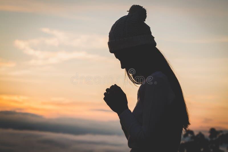 Le mani cristiane della donna che pregano alla donna del dio pregano per il blessi del dio immagini stock