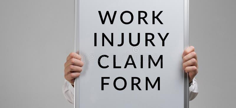 Le mani degli uomini che tengono un manifesto con la forma dell'iscrizione con un reclamo della lesione sul lavoro su un fondo le fotografia stock