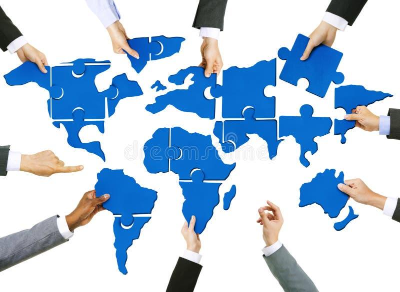 Le mani degli uomini d'affari con il puzzle di cartografia immagini stock libere da diritti