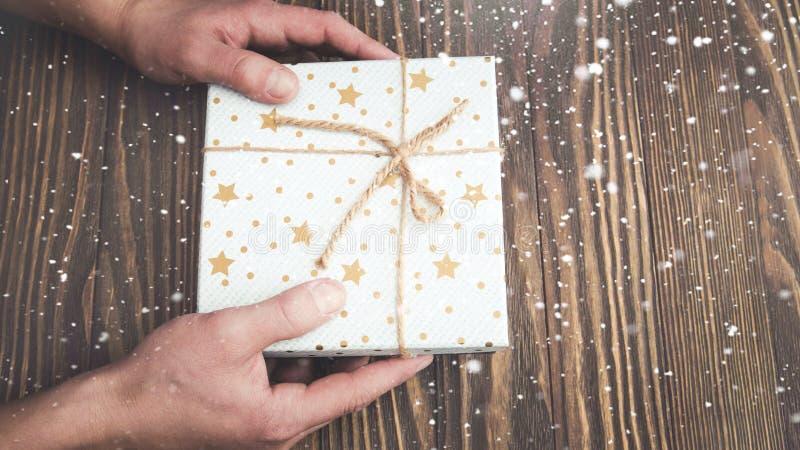 Le mani degli uomini hanno annodato il contenitore di regalo della corda, il regalo per il Natale ed il nuovo anno, fondo di nata immagini stock