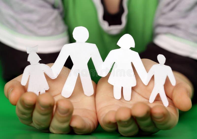 Le mani dei bambini che tengono una famiglia di carta fotografia stock