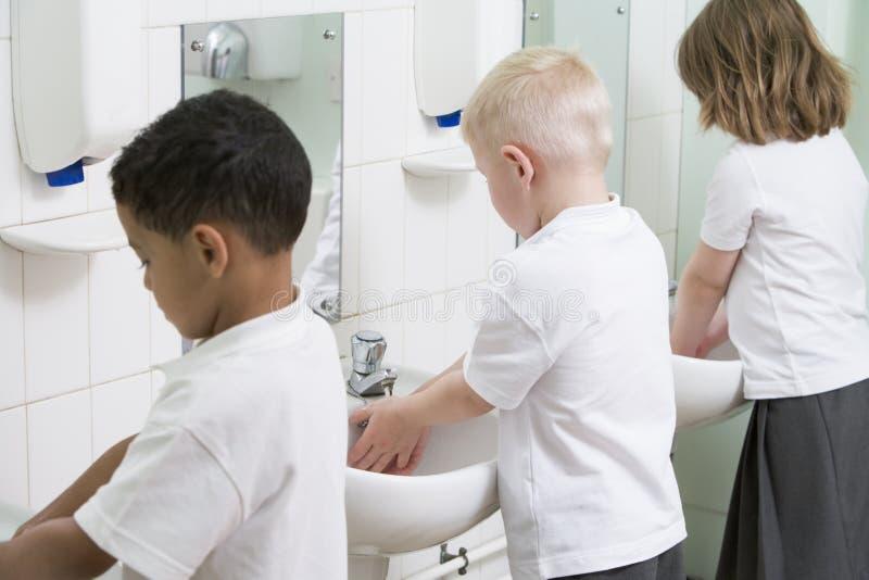 le mani dei bambini della stanza da bagno istruiscono il loro lavaggio immagine stock libera da diritti