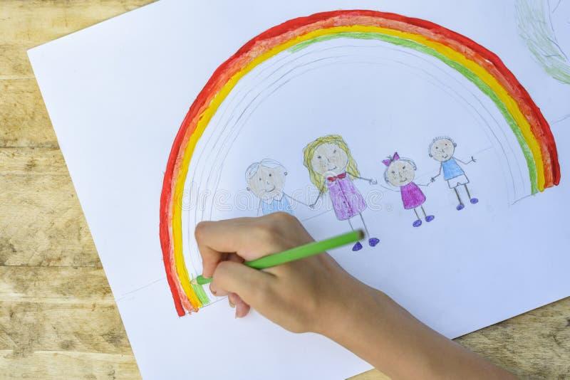 Le mani dei bambini dipingono un disegno con una spazzola e le pitture principale vi immagini stock libere da diritti