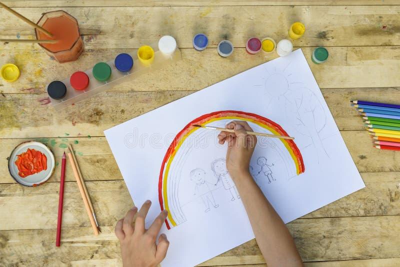 Le mani dei bambini dipingono un disegno con una spazzola e le pitture principale vi fotografia stock