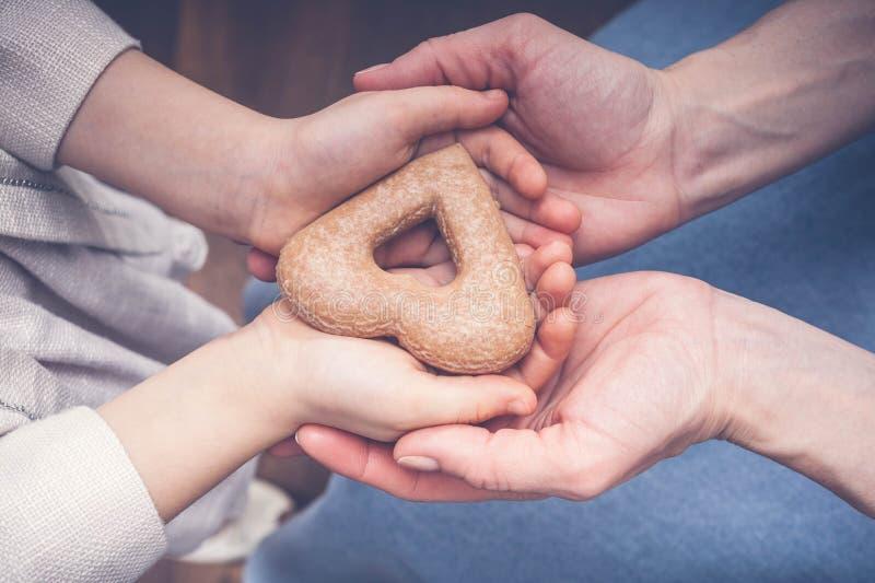 Le mani dei bambini e femminili tengono i biscotti sotto forma di cuore Concetto entro la festa della Mamma Tonalità d'annata immagini stock
