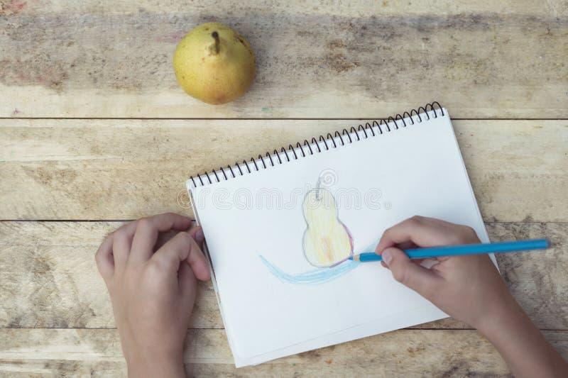 Le mani dei bambini estraggono una pera con le matite colorate Vista superiore fotografia stock libera da diritti