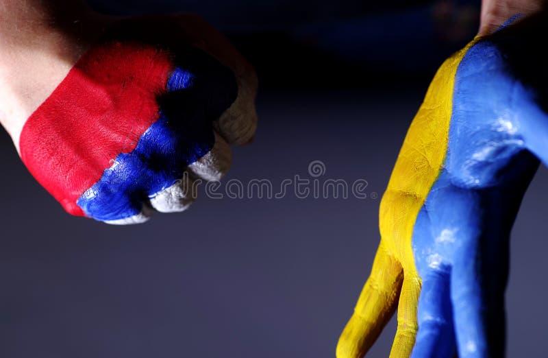 Le mani dei bambini sono colore dipinto di una bandiera dell'Ucraina e la Russia L'Ucraina e la Russia fotografia stock