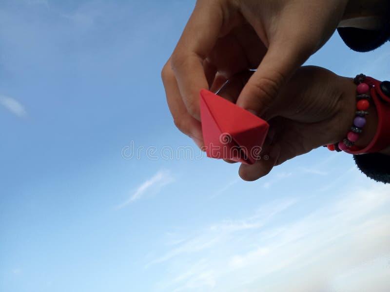 Le mani dei bambini tengono le navi di carta con il fondo del cielo blu Lavoro di gruppo e concetto di unità immagini stock
