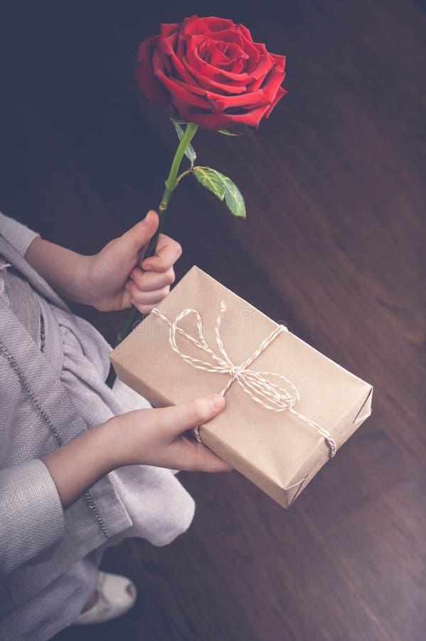 Le mani dei bambini tengono una grande rosa e un regalo Giorno felice del `s della madre tonalità immagini stock