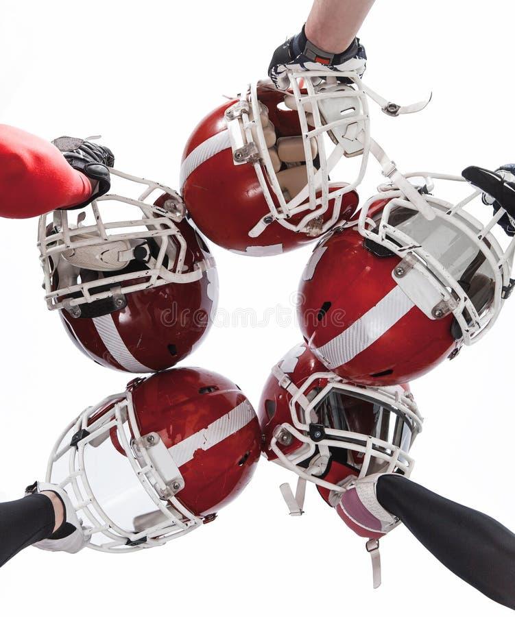 Le mani dei giocatori di football americano con i caschi su fondo bianco immagini stock libere da diritti
