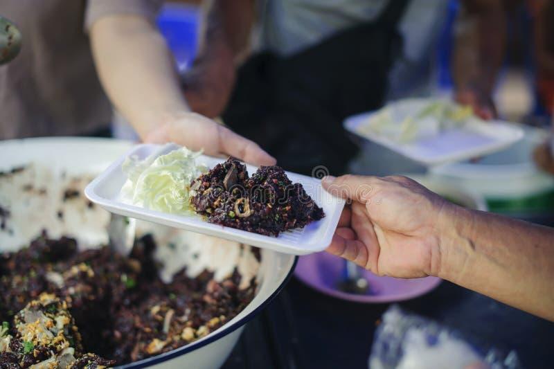 Le mani dei volontari serve l'alimento libero al povero e bisognoso nella città: La gente povera porta un contenitore per scavare immagini stock