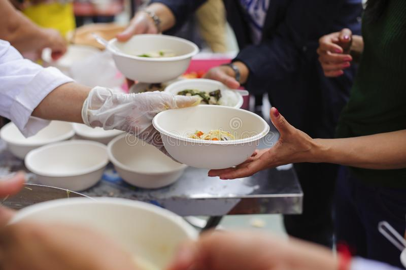 Le mani dei volontari serve l'alimento libero al povero e bisognoso nella città: La gente povera porta un contenitore per scavare fotografie stock libere da diritti