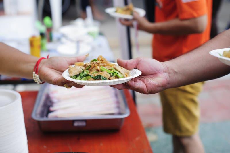 Le mani dei volontari serve l'alimento libero al povero e bisognoso nella città: La gente povera porta un contenitore per scavare fotografia stock libera da diritti