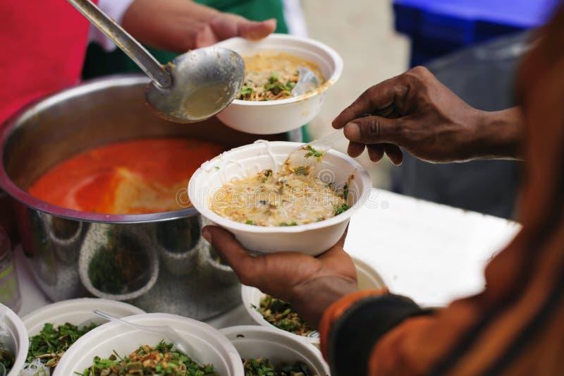 Le mani dei volontari serve l'alimento libero al povero e bisognoso nella città: La gente povera porta un contenitore per scavare immagini stock libere da diritti