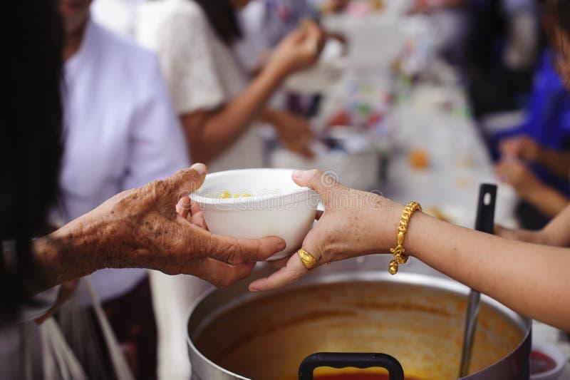 Le mani dei volontari serve l'alimento libero al povero e bisognoso nella città: La gente povera porta un contenitore per scavare immagine stock