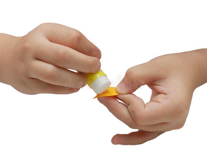 Le mani del bambino applicano la colla su un documento immagine stock libera da diritti