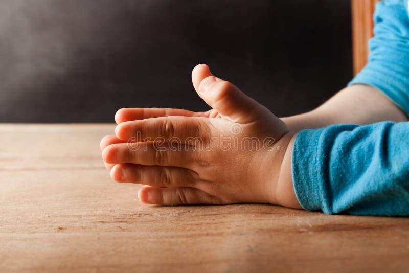 Le mani del bambino sono piegate per la preghiera fotografia stock libera da diritti